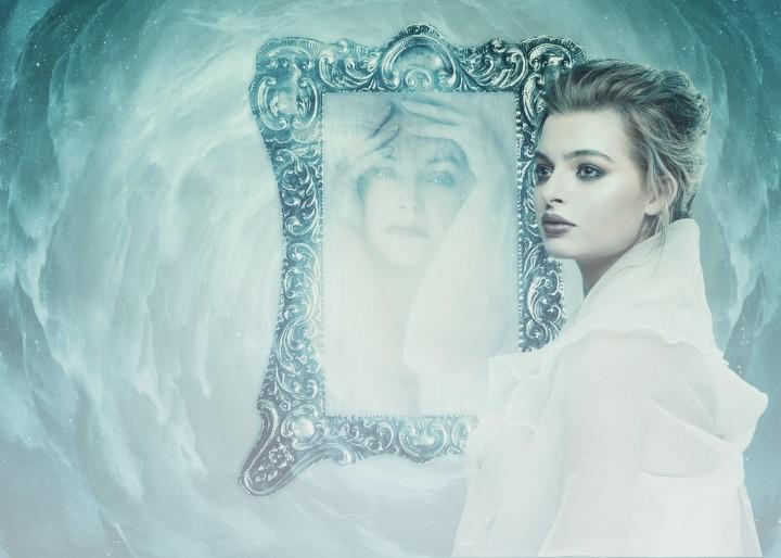 Frau vor Spiegel, die nur im Spiegel die Hände über dem Kopf zusammenschlägt