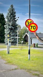 Neues Tempolimit von 70 wird von einer Hand aus dem Off über ein 30 iger Tempolimit Schild gehängt