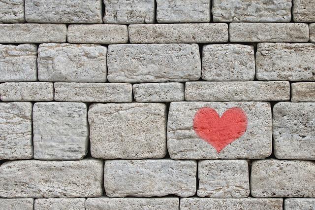 Graue Mauer mit Herz auf einen Stein gemalt