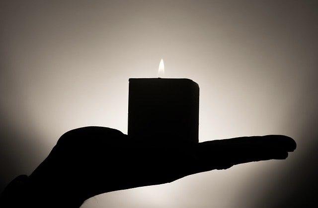 Angezündete Kerze auf Hand nach Feuer-Meditation