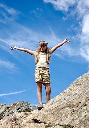 Mädchen auf Felsen in Siegerpose