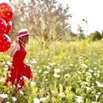 Junge Frau mit rotem Kleid läuft über eine Blumenwiese. In der Hand hält sich viele rote Luftballons