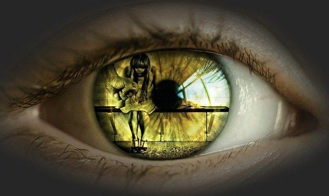 In der Iris eines Auges ist ein misshandeltes Kind zu sehen, welches zusammen gekauert auf einer Bank sitzt