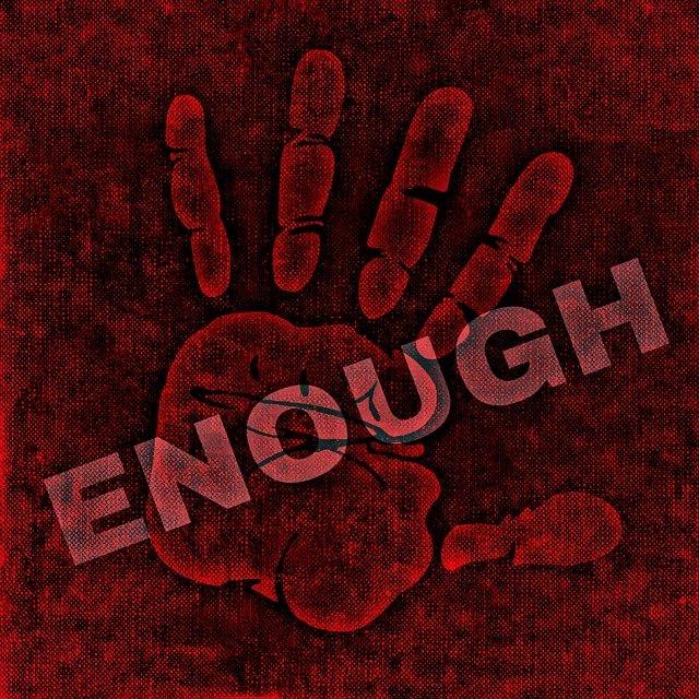 Auf einer gemalten, abwehrenden Hand steht das Wort ENOUGH