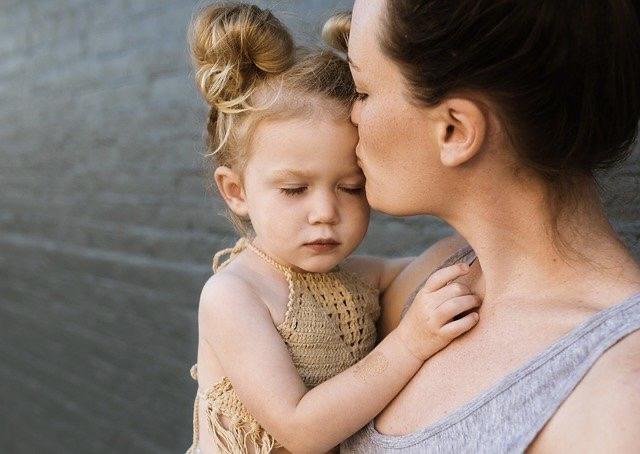 Kleines Mädchen lässt sich auf dem Arm der Mama trösten