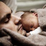 Neugeborenes liegt auf Brust des Vaters