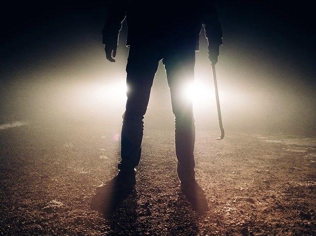 Mann steht vor Lichtquelle, Man sieht nur den unteren Teil seines Körpers als Schatten. In der Hand hält er ein Schlaginstrument