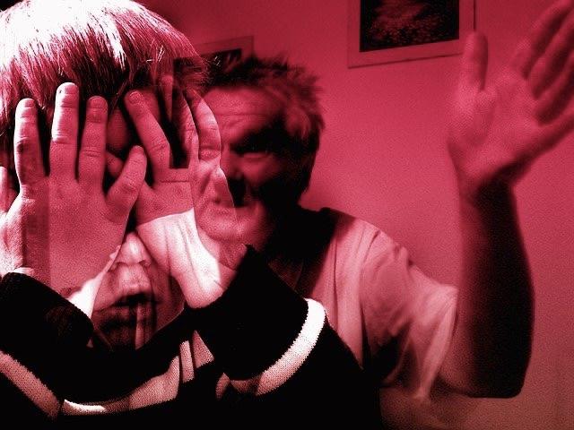 Kind im Vordergrund nimmt schützend die Hände vor das Gesicht und wendet sich ab, weil Vater im Hintergrund die Hand erhebt. Magenta eingefärbtes Bild