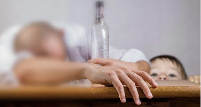 Betrunkener Vater auf Tisch eingeschlafen, unscharf, dahinter kleines Kind schaut über Tischrand, scharf