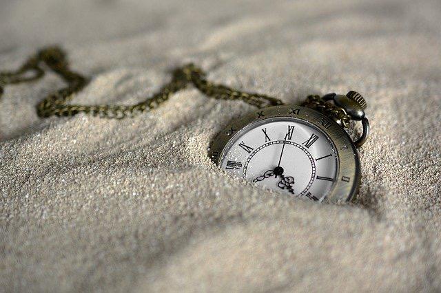 Taschenuhr versinkt im Sand