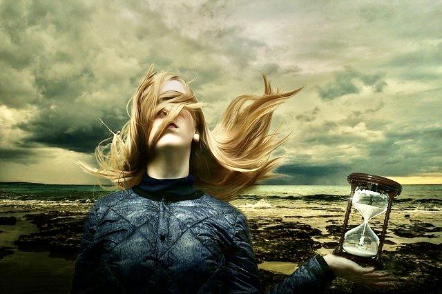Traumsequenz, Frau mit ins Gesicht gewehten Haaren, mit Sanduhr im Hintergrund