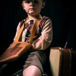 Ein Junge vor schwarzem Hintergrund mit Capi und Kleidung von früher, guckt spitzbübisch. Er hat eine große Tasche umgehängt