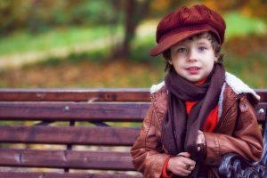 Junge mit Capi und Schal um den Hals, sitzt allein, aber verschmitzt guckend auf einer Bank im Park
