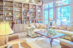 Wohnzimmer mit Tisch, Sofa, Wandregalen und großer Fensterfront
