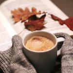 Herbstblätter liegen auf Buch, Ärmel umfassen einen heißen Becher Schokolade