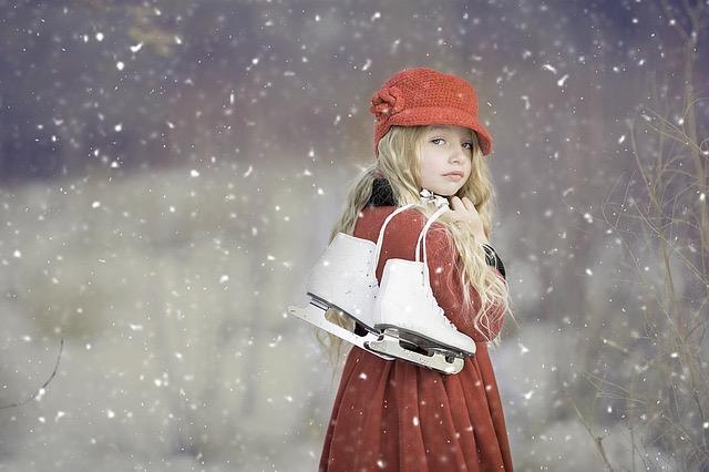 Mädchen, rot und winterlich gekleidet, trägt Schlittschuhe über der Schulter. Es schneit.