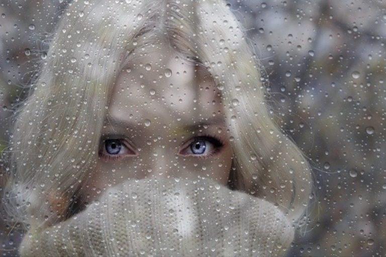 Hübsche Frau mit blauen Augen mit Regenbild überblendet, Tropfen vor dem Gesicht