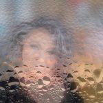 Frau unscharf hinter Scheibe voller Wassertropfen