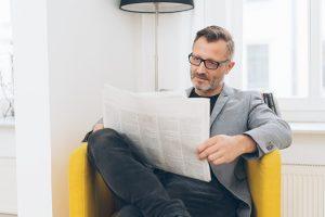 Lesender Mann mit Brille in Sessel