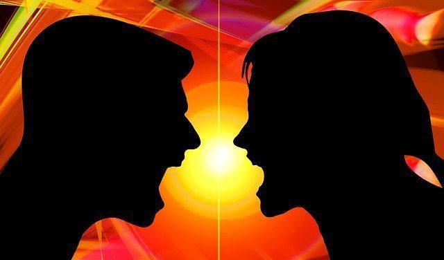Ein Paar, als Silhouetten erkennbar, schreit sich vor feurigem Hintergrund an