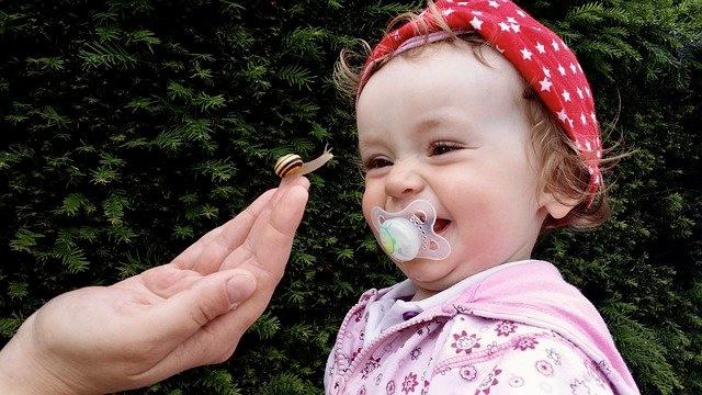 Lust am Leben - Kleines Kind mit Schnuller im Mund beobachtet Schnecke auf Hand der Mutter und lacht darüber