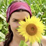 Lust am Leben - Hübsche junge Frau versteckt sich halb hinter Sonnenblume