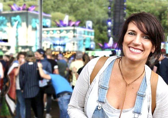 Frau lachend vor einem von vielen Menschen besuchtes Fest. Sie strahlt, als hätte sie viel Freude.