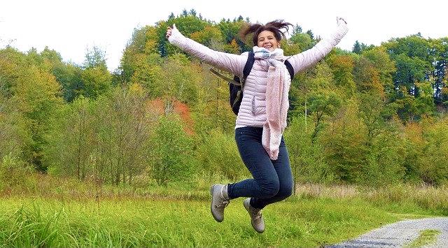 Lebensfreude - Luftsprung einer jungen Frau im Grünen