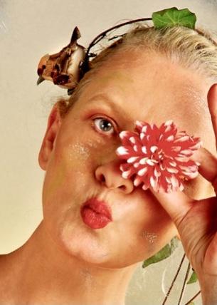 Frau albert herum, indem sie sich eine Blüte vor ihr linkes Auge hält und einen Haarreif mit Vögelchen daran, trägt.