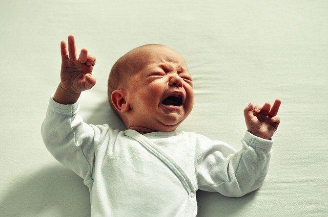 Baby im Bett liegend und schreiend