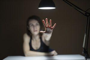 Frau hebt abwehrend Hand