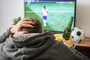Mann rauft sich die Haare beim Fußball gucken im Fernsehen, Bier in der Hand