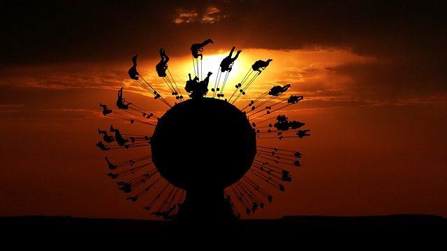 Kettenkarussell voller Menschen in der Dämmerung bei Sonnenuntergang