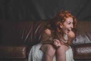 Frau in weißem Kleid auf Sofa lacht schallend